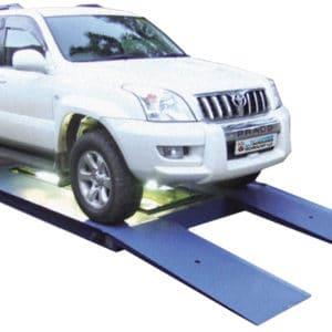 Das zu überprüfende Fahrzeug fährt auf eine niedrige Rampe und ein Kamerasystem überprüft die Fahrzeugkarosserie